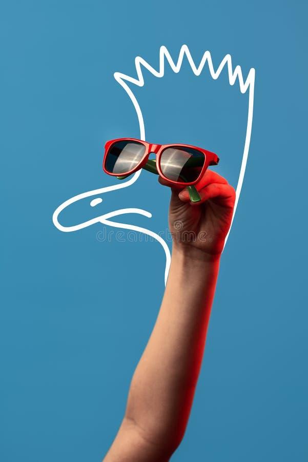 Tecknad filmstruts med en Mohawk i trendig solglasögon på blå bakgrund royaltyfri foto