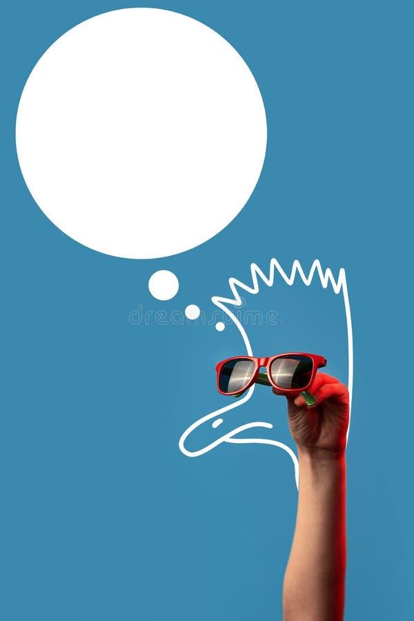 Tecknad filmstruts med en Mohawk i trendig solglasögon på blå bakgrund arkivfoton