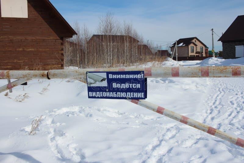Tecknet för video bevakning för uppmärksamhet är det varnande på plattan på den stängda barriären i byn nära husen passagen stäng royaltyfria foton