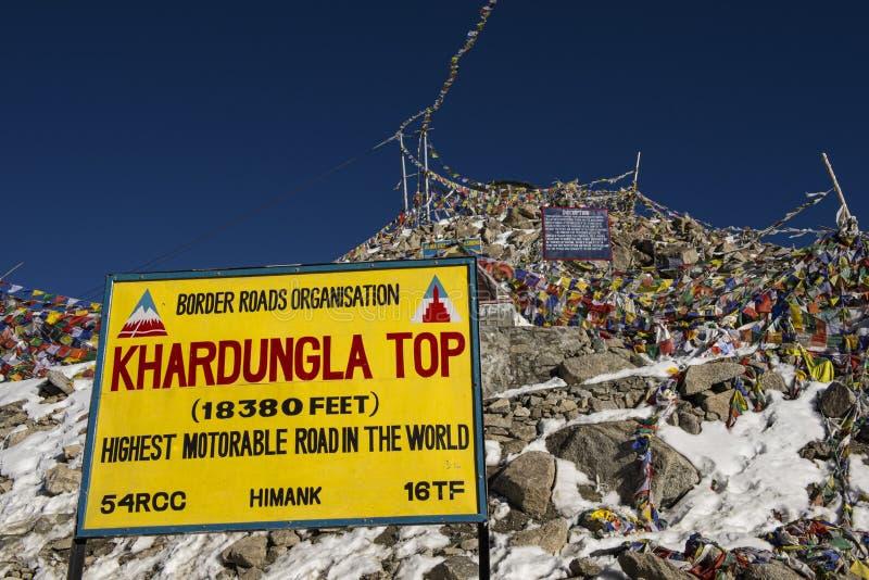 Tecknet och tibetana bönflaggor på Khardung La passerar Ladakh, Indien arkivfoton