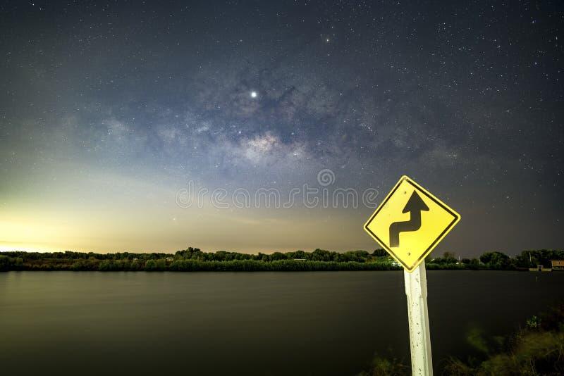 Tecknet tecken, akta sig av kurvor på natten, bak tecknet med Vintergatan royaltyfri fotografi