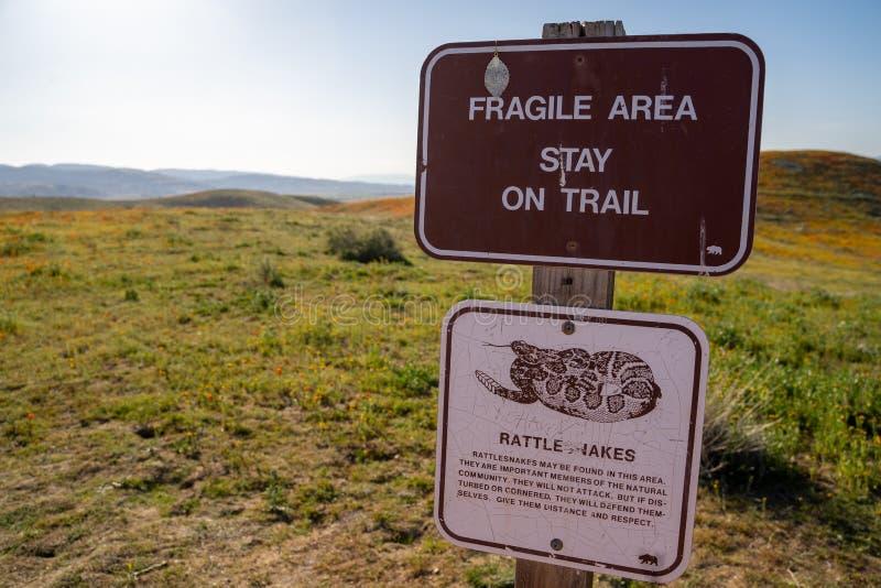 Tecknet varnar turister på antilopdalen Poppy Reserve att bli på slingan för att bevara arkivbild