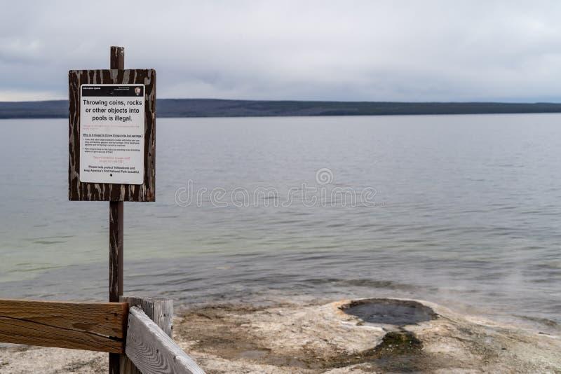 Tecknet varnar Yellowstone nationalparkbesökare att inte kasta avfall i tipsen och geysersna för varm vår arkivfoton