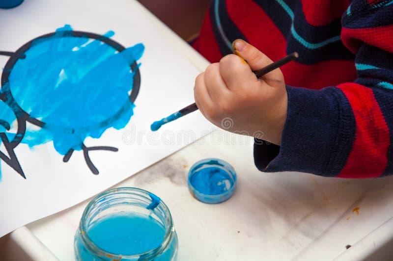 Teckning för barn` s Hand av den barnteckningsmålarfärgerna och borsten royaltyfria foton