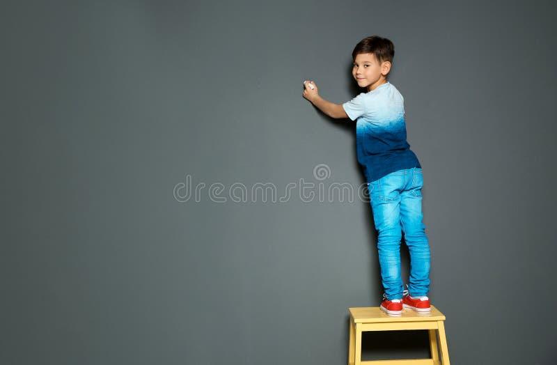 Teckning för litet barn med krita på den gråa väggen royaltyfri fotografi