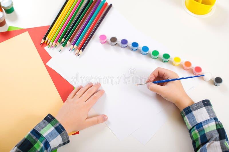 Teckning för unge` s Konstbakgrund med färgrika blyertspennor, målarfärger och tomt papper Ungehänder med borsten på ett papper B fotografering för bildbyråer