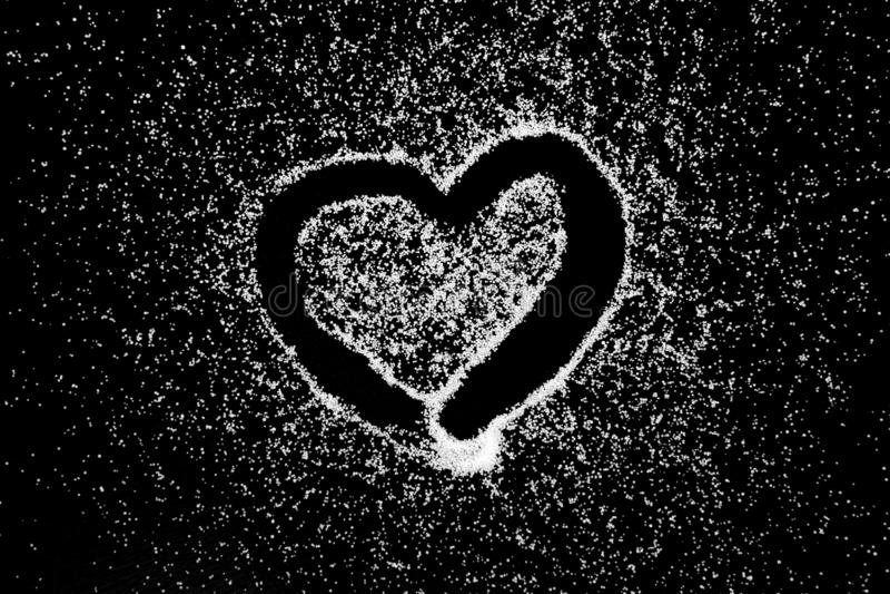 Teckningen för förälskelsehjärtasymbolet vid fingret på vit saltar pulver på svart brädebakgrund royaltyfria foton