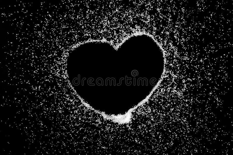 Teckningen för förälskelsehjärtasymbolet vid fingret på vit saltar pulver på svart brädebakgrund fotografering för bildbyråer