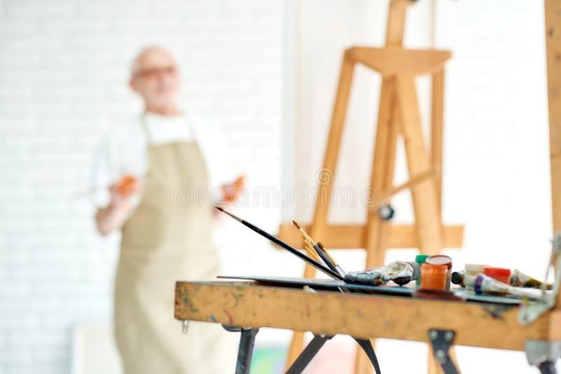 Teckningsinstrument och staffli med den manliga konstnären på suddighetsbakgrund på studion arkivfoton