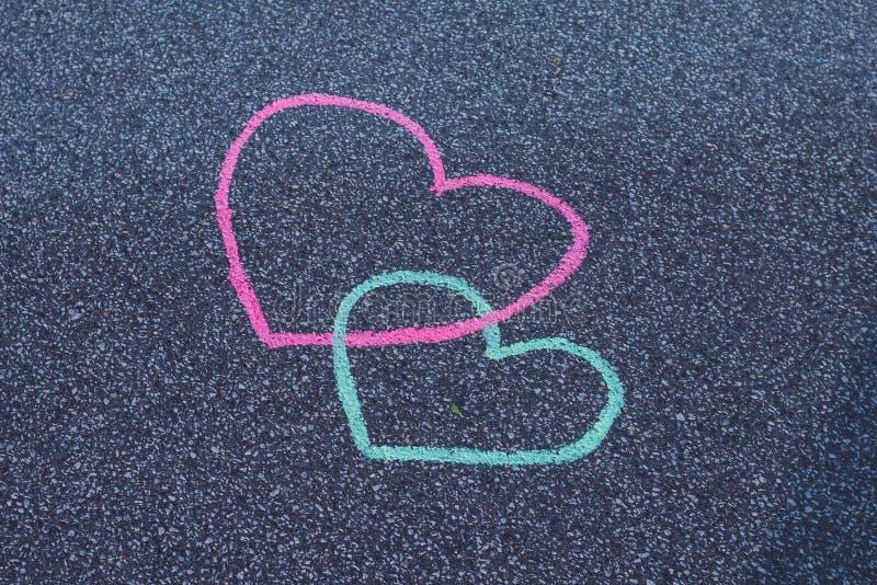Teckningskrita för två hjärtor på asfalten royaltyfria foton