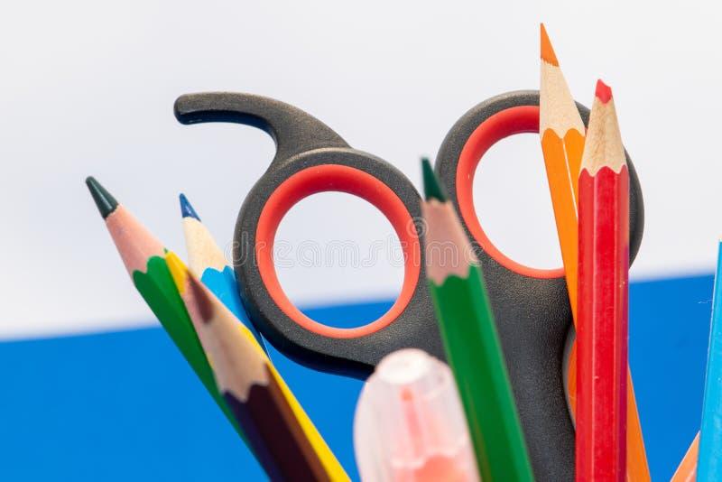 Teckningsmaterial liksom blyertspennor, vässare eller sax på skola arkivbild
