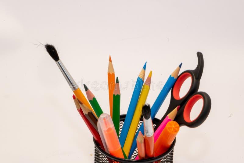 Teckningsmaterial liksom blyertspennor, vässare eller sax på skola arkivfoto