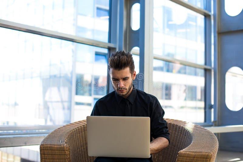 Teclado acertado del empresario del hombre en el cuaderno durante día del trabajo en empresa imagenes de archivo
