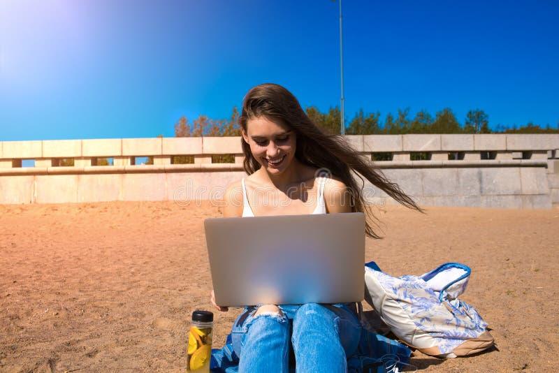 Teclado alegre de la muchacha del inconformista en netbook fotografía de archivo