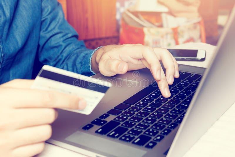 Teclado de datilografia asiático do portátil do homem novo e guardar o cartão de crédito w foto de stock