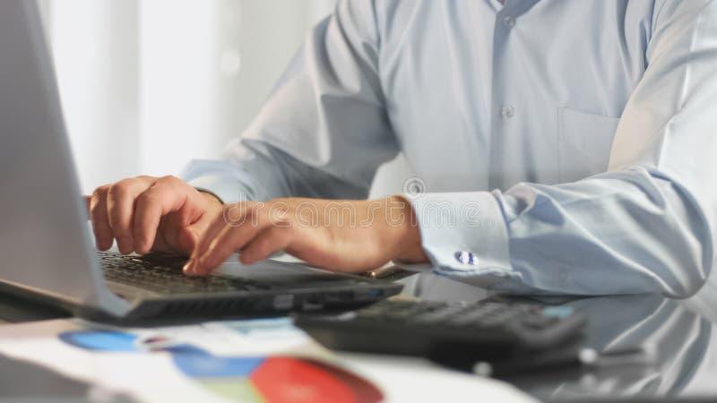 Teclado de datilografia do portátil do gestor de escritório, analista financeiro que prepara o relatório, trabalho imagens de stock royalty free