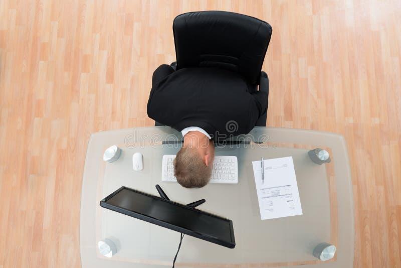 Teclado de Leaning On Computer do homem de negócios fotografia de stock