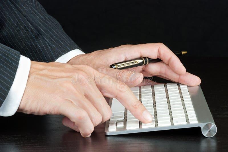 Teclado de ordenador de Pushes Enter On del hombre de negocios fotos de archivo