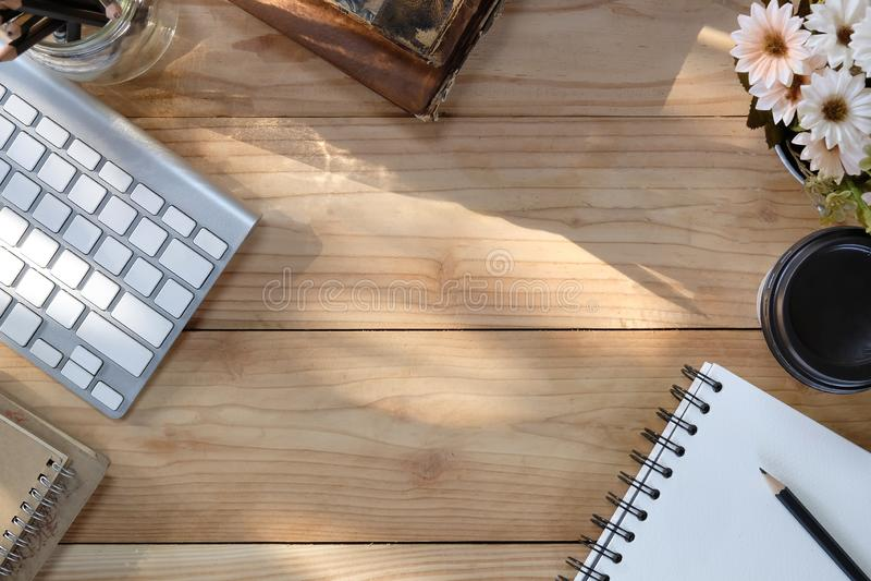 Teclado de ordenador del escritorio de oficina, café, flor, cuaderno en la tabla de madera y luz de la mañana con la visión super foto de archivo