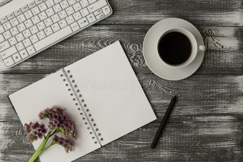 Teclado de ordenador de la visión superior, cuaderno en blanco y taza de café y de flores rosadas en la tabla de madera gris imagenes de archivo