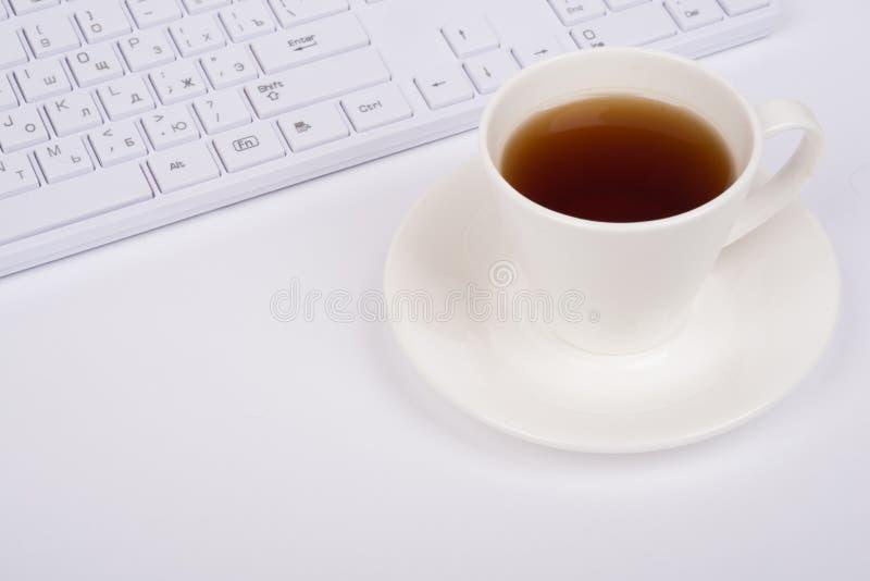 Teclado de ordenador y taza de café blancos, visión superior foto de archivo libre de regalías