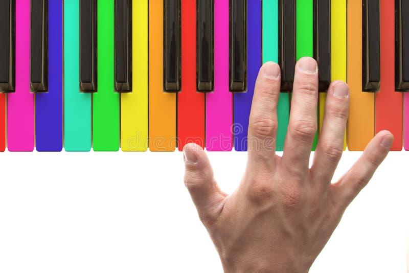 Teclado de piano do arco-íris com mão fotos de stock royalty free
