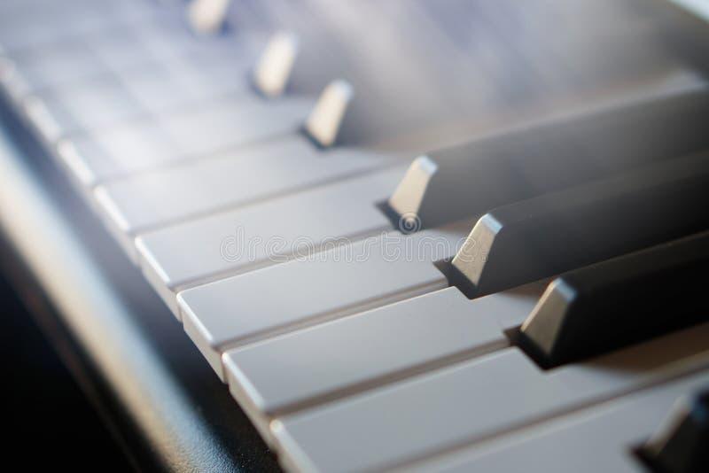 Teclado de piano electrónico del sintetizador en la macro de los rayos del sol fotos de archivo