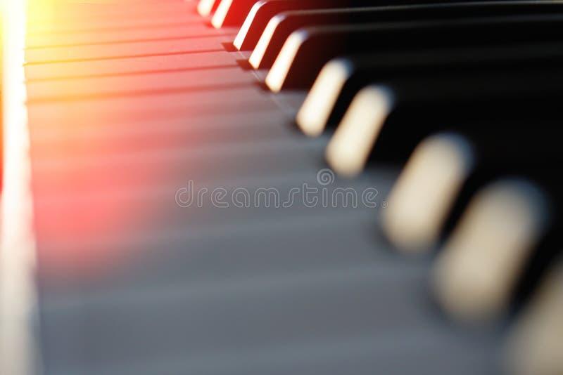 Teclado de piano electrónico del sintetizador en la macro de los rayos del sol foto de archivo libre de regalías