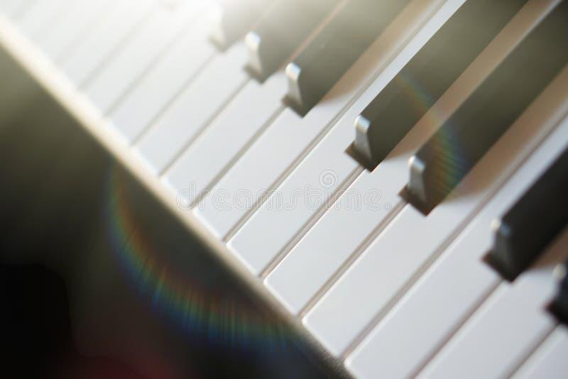 Teclado de piano electrónico del sintetizador en la macro de los rayos del sol fotografía de archivo