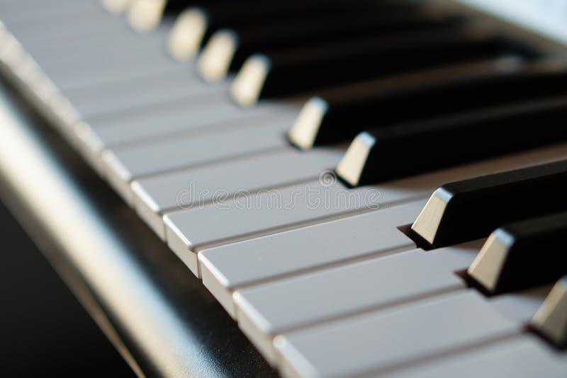 Teclado de piano electrónico del sintetizador en la macro de los rayos del sol foto de archivo