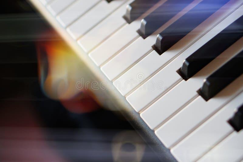 Teclado de piano electrónico del sintetizador en la macro de los rayos del sol imagen de archivo