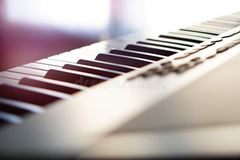 Teclado de piano electrónico del sintetizador en la macro de los rayos del sol imagen de archivo libre de regalías