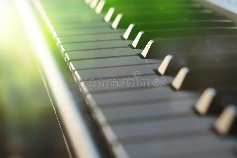 Teclado de piano electrónico del sintetizador en la macro de los rayos del sol fotos de archivo libres de regalías