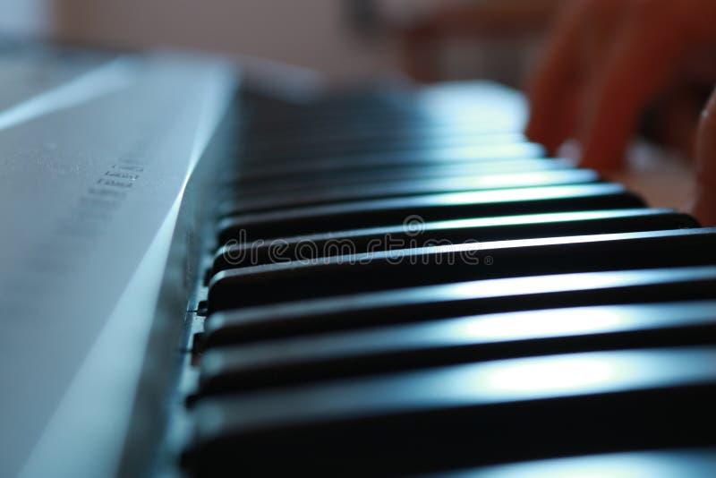 Teclado de um piano com uma mão fotos de stock