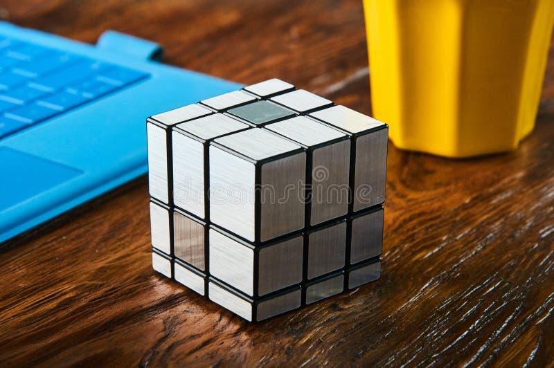 Teclado del ordenador portátil de la composición del cubo del ` s de Rubik en la tabla imágenes de archivo libres de regalías