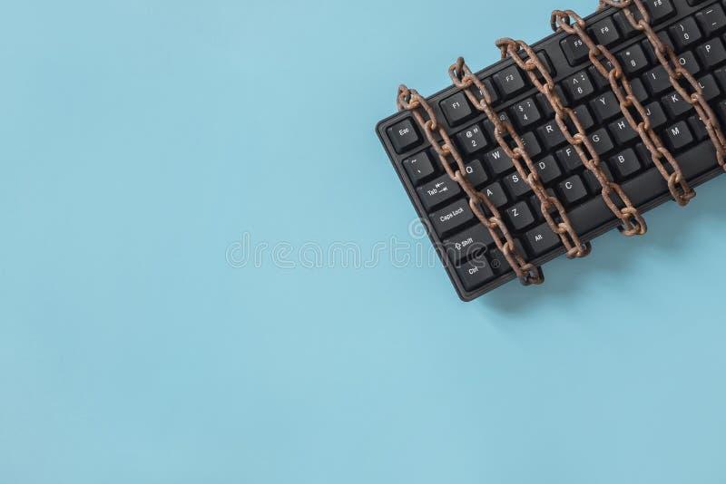 Teclado negro con una cadena en espiral Concepto para el tema de la censura o de la libertad de prensa fotos de archivo libres de regalías