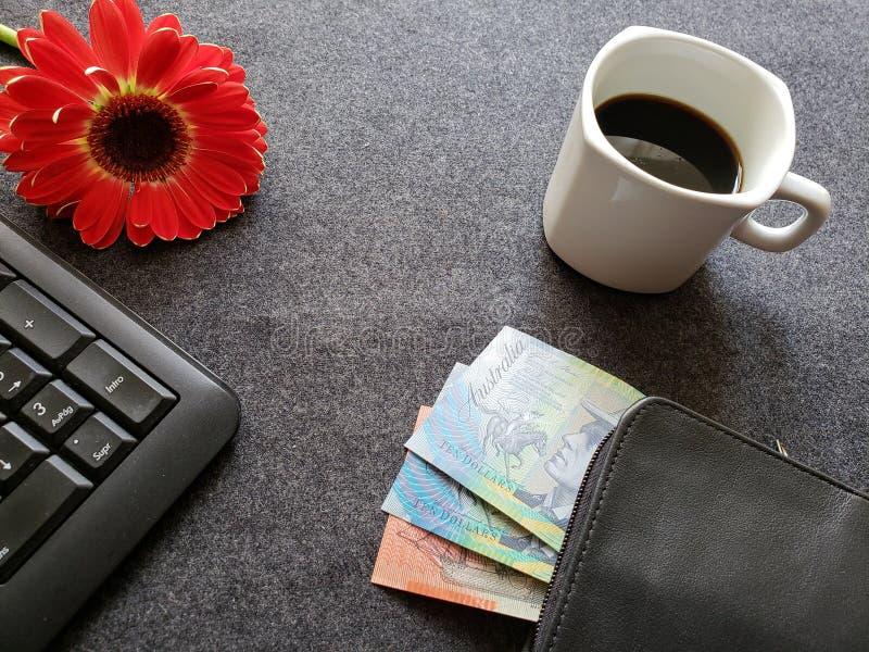 teclado numérico de um computador, de uma flor do gerbera, de um copo de café e de uma carteira preta com as cédulas dos dólares  fotografia de stock
