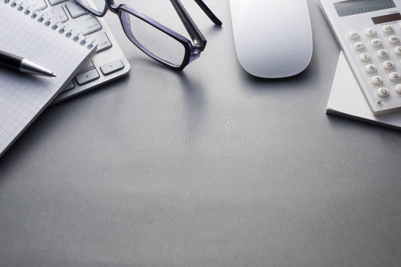 Teclado, rato e materiais de escritório em Grey Desk foto de stock royalty free