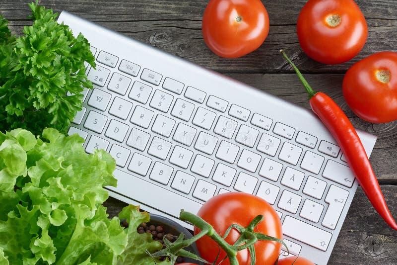 Teclado y verduras Búsqueda en línea de la receta fotografía de archivo