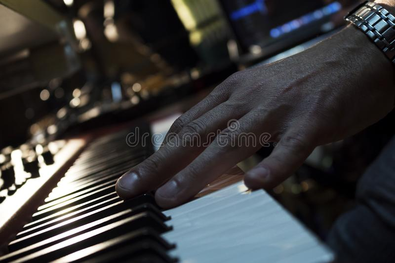 Teclados de piano no estúdio da música e em uma mão de um músico fotografia de stock royalty free
