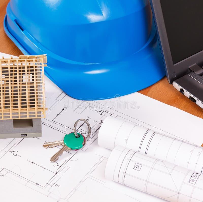 Teclas HOME, casa pequena, diagramas elétricos com o portátil para trabalhos na mesa, conceito do coordenador da casa da construç imagens de stock royalty free