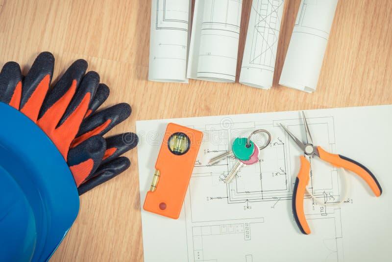 Teclas HOME con los dibujos el?ctricos, el casco azul protector con los guantes y las herramientas anaranjadas del trabajo, conce fotos de archivo libres de regalías