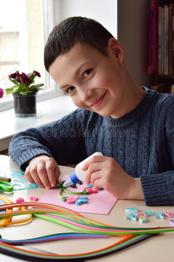 Tecnica di Quilling Ragazzo che fa le decorazioni o la cartolina d'auguri Strisce di carta, fiore, forbici Mestieri fatti a mano  immagini stock libere da diritti