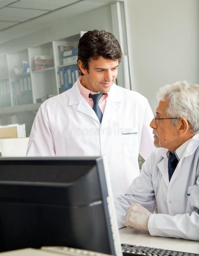 Tecnici che discutono nel laboratorio immagine stock