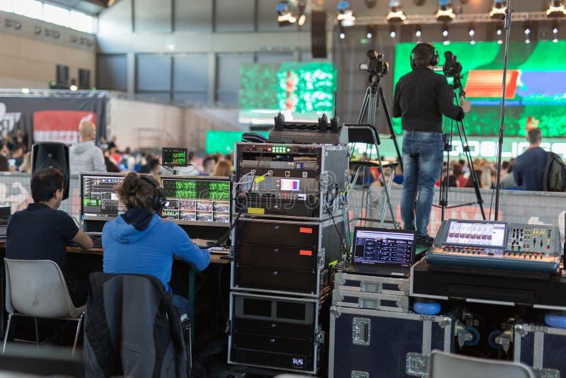 Tecnici dell'illuminazione e del suono e operatori televisivi sul lavoro in BackStage durante un evento pubblico fotografia stock libera da diritti