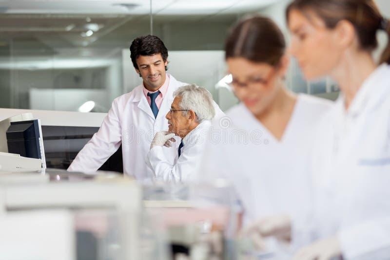 Tecnici maschii che discutono nel laboratorio immagini stock libere da diritti