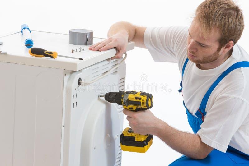 Tecnician que fixa uma máquina de lavar foto de stock