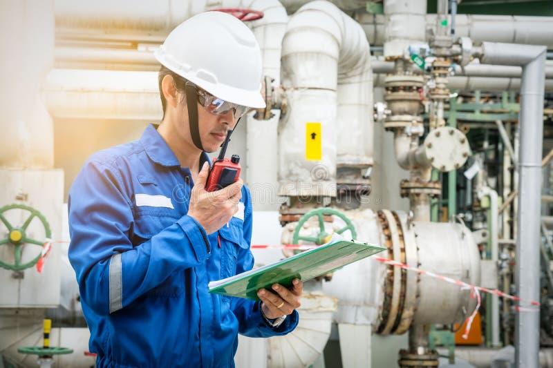 Tecnico asiatico che lavora con il walkie-talkie e la lista di controllo fotografie stock libere da diritti