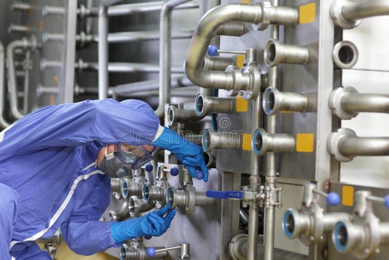 Tecnico in camici che mantiene sistema tecnologico in pianta immagine stock libera da diritti