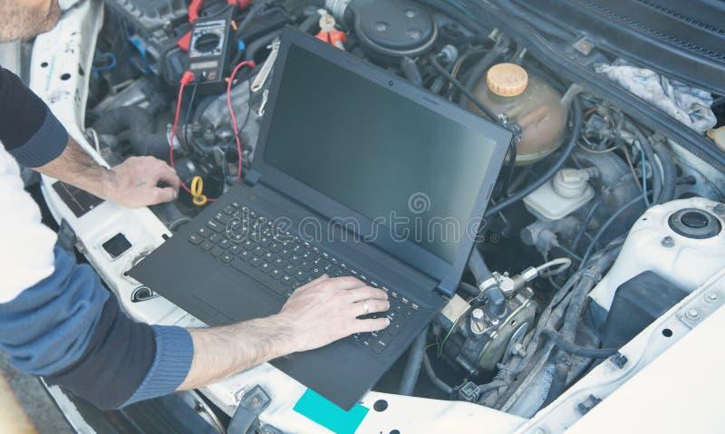 Tecnico che controlla il motore di automobile con un computer portatile usando immagine stock